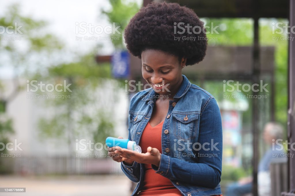 African woman disinfecting her hands - Royalty-free 25-29 Years Stock Photo