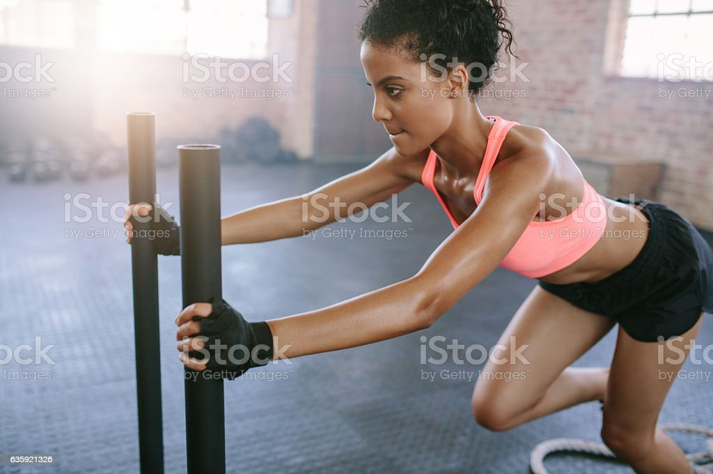 African woman doing intense workout in gym stock photo