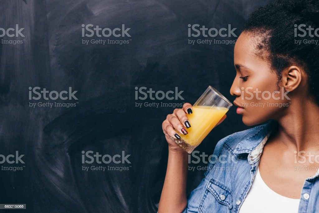 African woman drink orange juice. Healthy life. 免版稅 stock photo