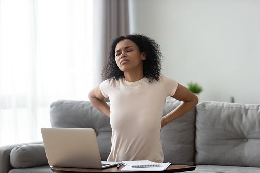 istock African woman feeling backpain tired of computer sit on sofa 1162624157