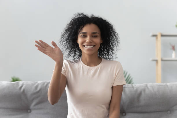 African woman feels happy wave hand looking at camera Happy african woman sit on couch wave hand looks at camera make video call use computer webcam view, instant virtual chat online communication, vlogger record webinar, job interview distantly concept analogue audio storage media stock pictures, royalty-free photos & images