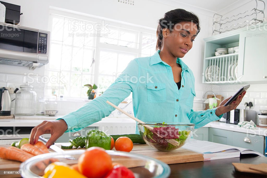 African woman following a recipes steps. stock photo