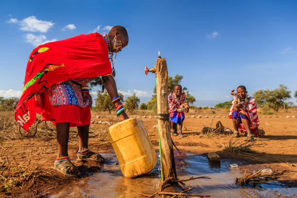 african woman from maasai tribe collecting water, kenya, east africa - village stock photos and pictures