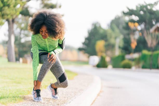african woman got sport injured while jogging on the street - caviglia foto e immagini stock
