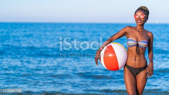 African woman having fun with beach ball at the beach