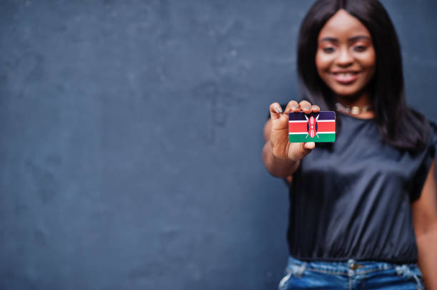 African woman hold small Kenya flag in hands. stock photo