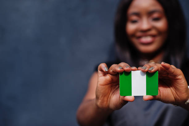 African woman hold small Nigeria flag in hands. stock photo