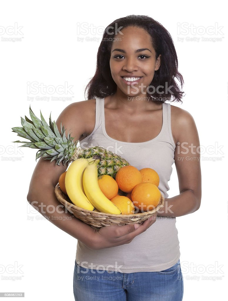 African woman holding a basket of fruits stock photo