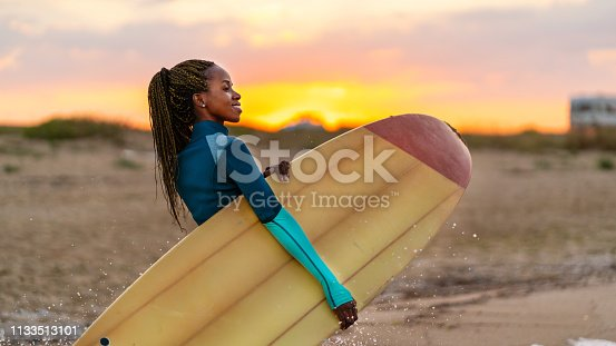 African woman holding surfboard and walking on the beach at sunset