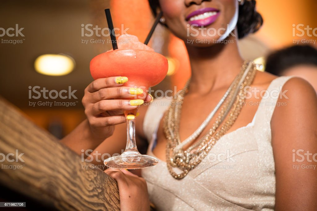African Woman in bar drinking cocktail stock photo