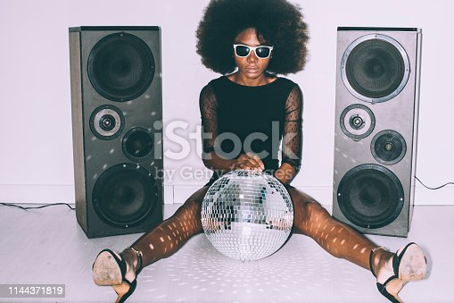 African woman in black dress and sunglasses sitting on floor and holding disco ball.