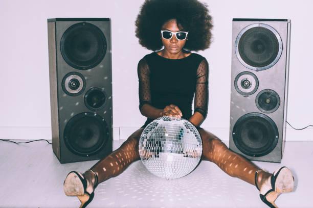 femme africaine dans la robe noire et les lunettes de soleil retenant la boule de disco - dance music photos et images de collection