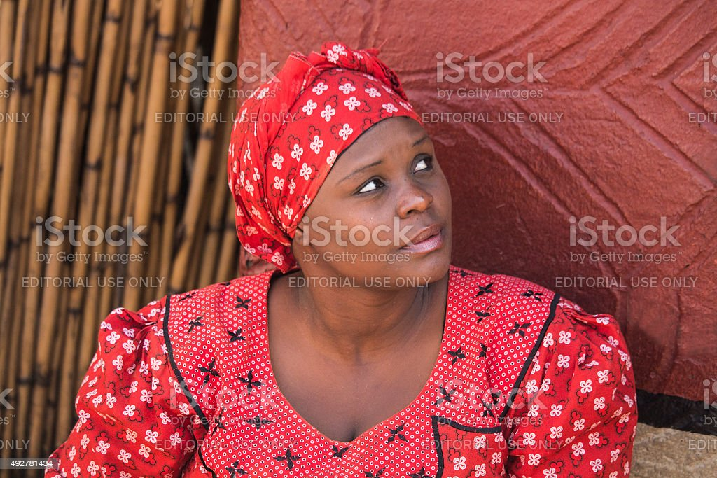 African woman in handmade red clothes next to her house. stock photo
