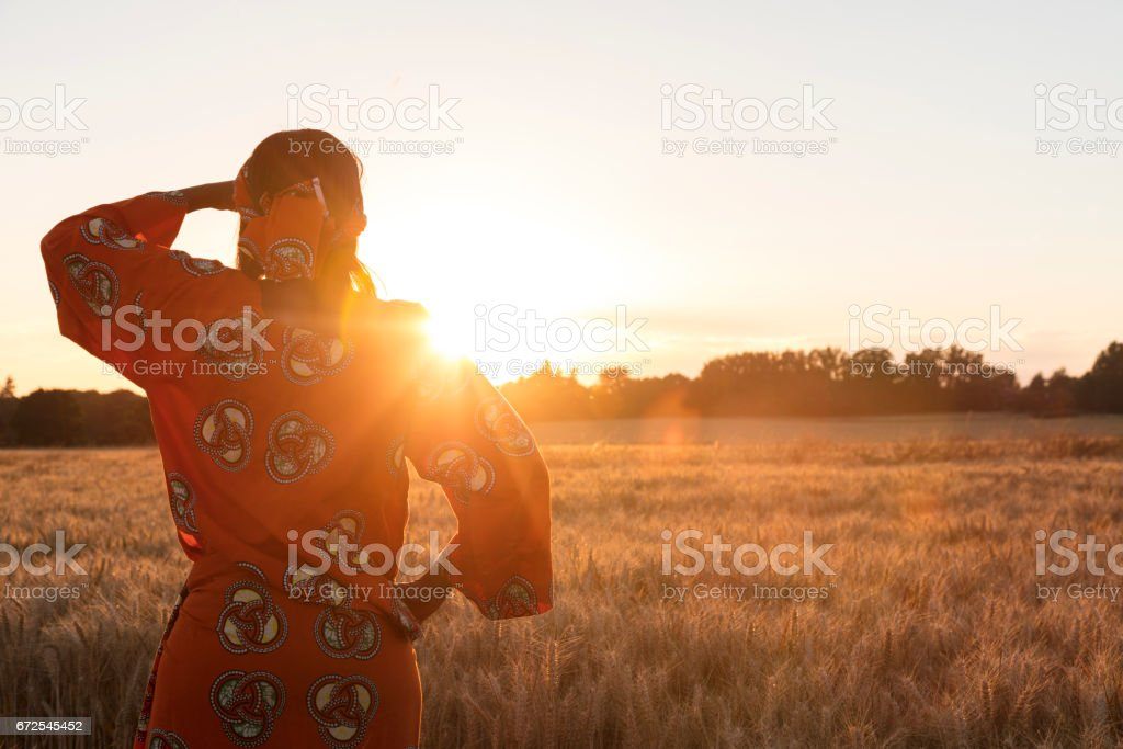 African woman in traditional clothes standing looking across a field of barley or wheat crops at sunset or sunrise - Photo