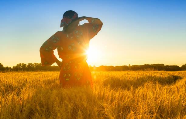 afrikansk kvinna i traditionella kläder stående, tittar, hand till ögon, i fältet av korn eller vete grödor på solnedgång eller soluppgång - afrika bildbanksfoton och bilder