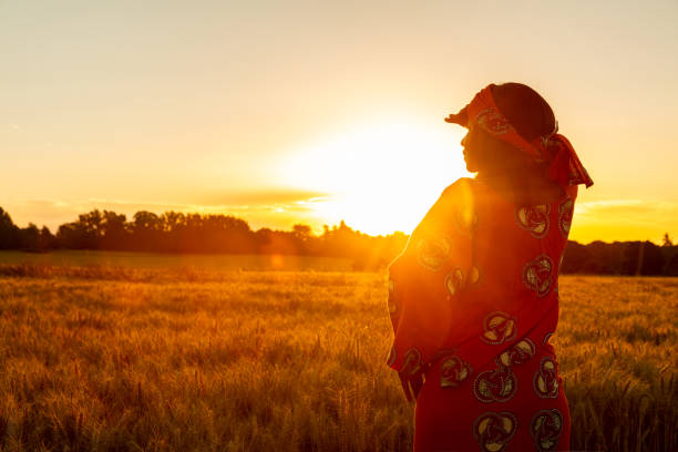 African woman in traditional clothes standing, looking, hand to eyes, in field of barley or wheat crops at sunset or sunrise African woman in traditional clothes standing, looking, hand to eyes, in field of barley or wheat crops at sunset or sunrise east africa stock pictures, royalty-free photos & images