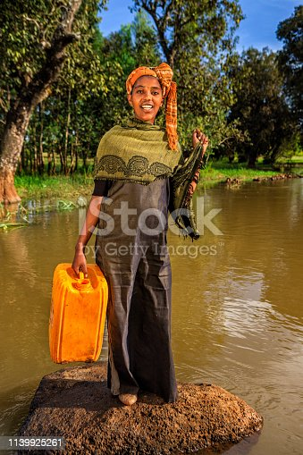 African woman is taking water from the river, African women and children often walk long distances to bring back jugs of water that they carry on their back.
