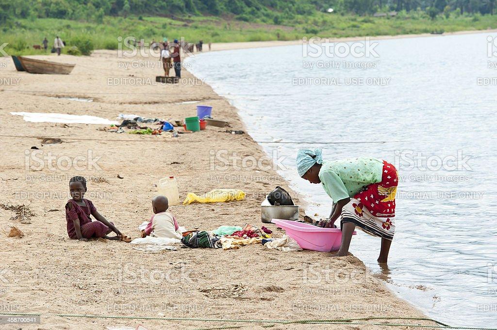 African woman is washing cloths in Lake Tanganyika, Burundi, Africa stock photo
