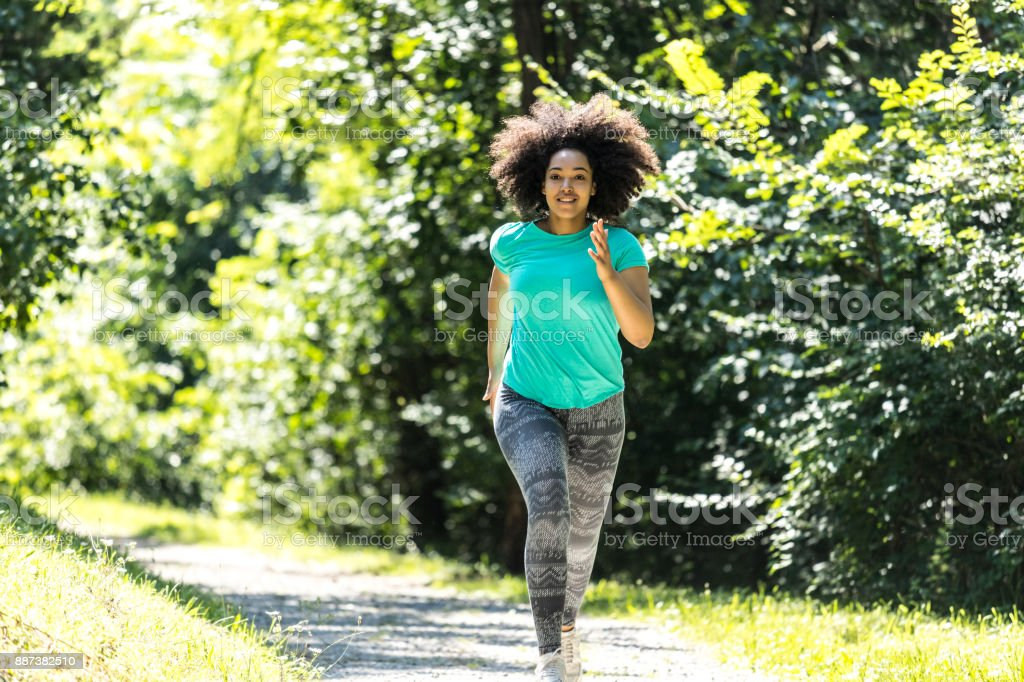 African woman jogging in park stock photo