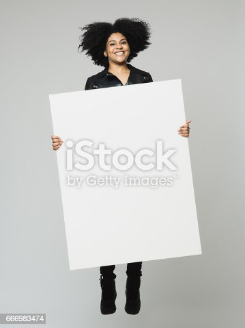 istock African woman jumping with a blank billboard 666983474