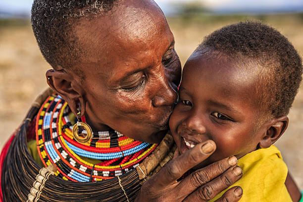 african woman kissing her baby, kenya, east africa - african culture stock photos and pictures