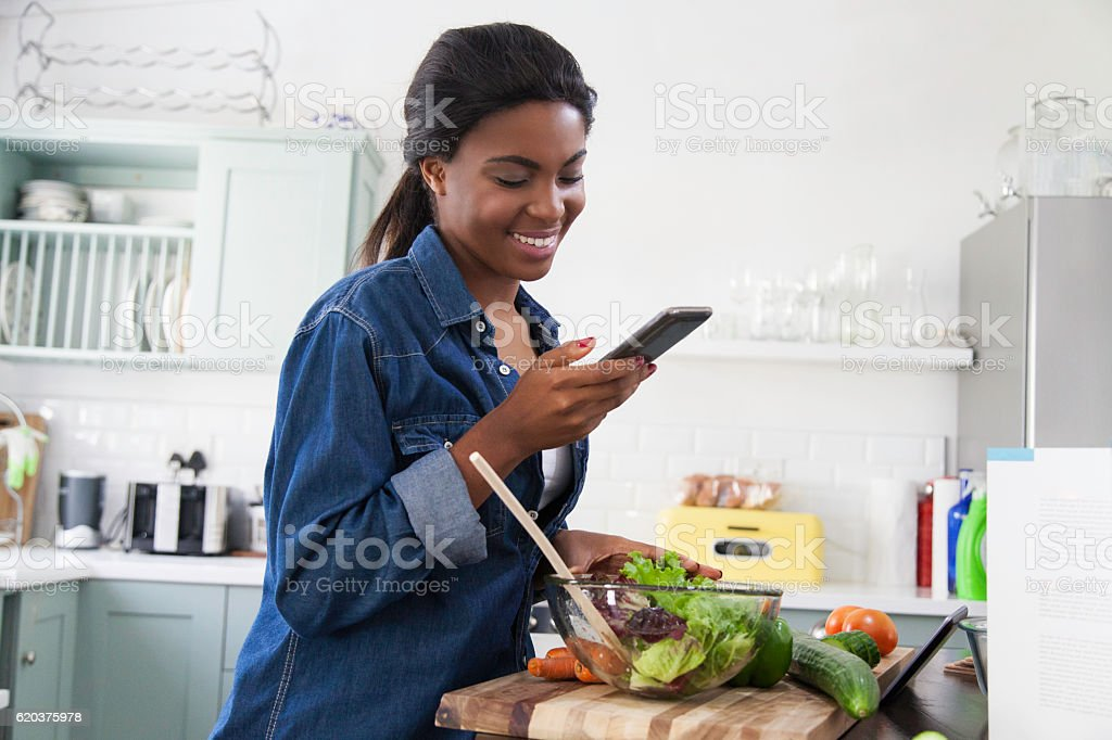 African woman laughing at a text message on her cellphone. stock photo