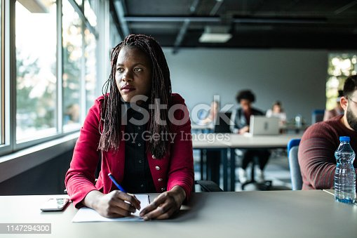 Close up  of young wistful African woman looking through the window  at the office space
