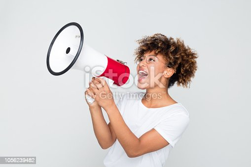Portrait of young afro american woman yelling into a megaphone on grey background. African female making an announcement with megaphone.