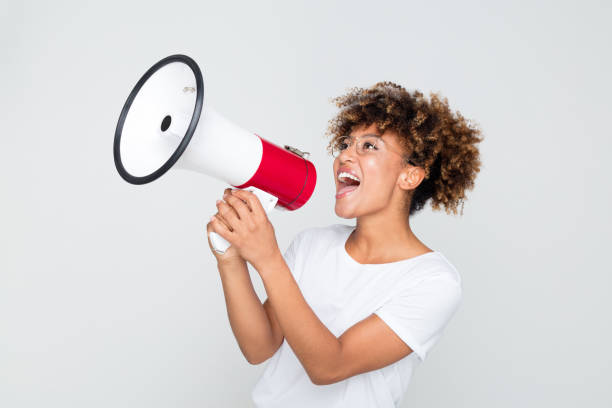 african woman making an announcement with megaphone - megafono foto e immagini stock
