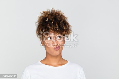 Close up portrait of doubtful afro american woman looking away and making a decision on grey background