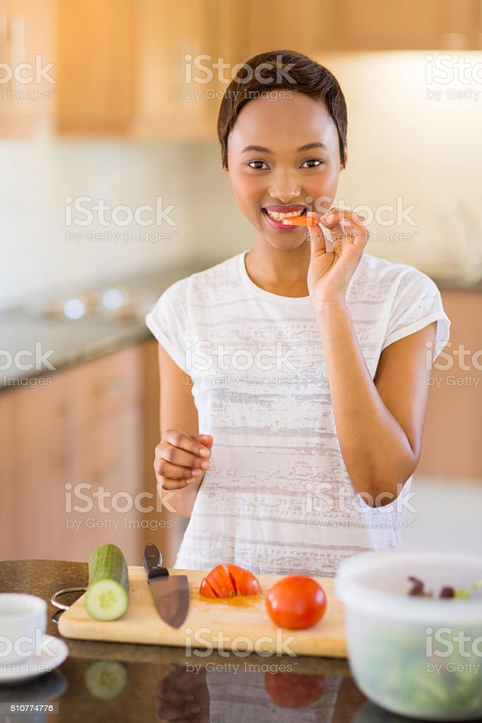 african woman making salad in kitchen stock photo