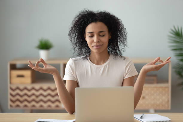 African woman meditating sitting at desk in front of laptop African woman meditating sit at desk in front of pc, serene mixed-race female closed eyes folded fingers mudra symbol do exercise practising yoga reducing anxiety stress positive frame of mind concept mental wellbeing stock pictures, royalty-free photos & images