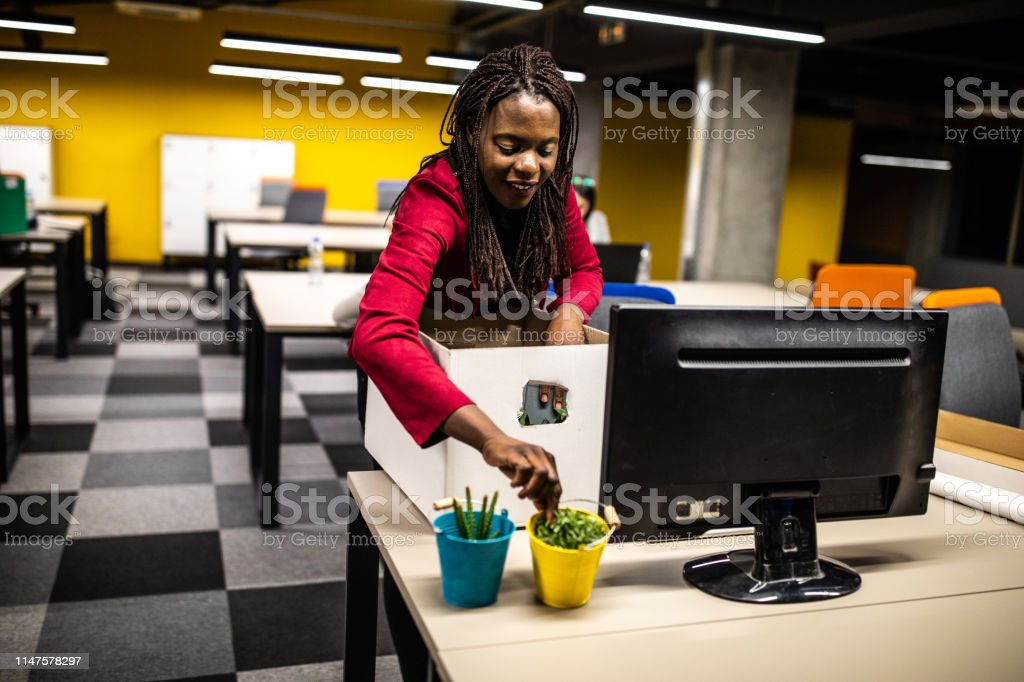 African woman unpacking her stuffs from cardboard box at new office,...