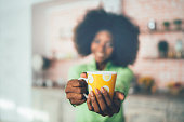 African woman holding coffee cup, focus on foreground.