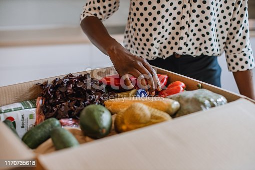 African woman opening parcel with meal kit.