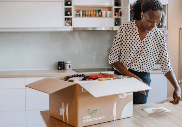 African Woman Opening Parcel With Meal Kit stock photo