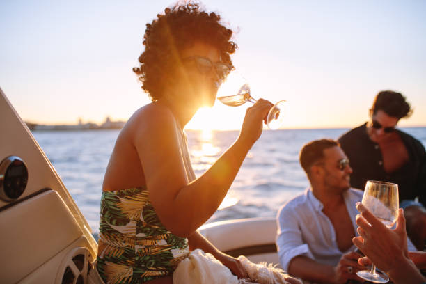 African woman partying with friends in boat - fotografia de stock