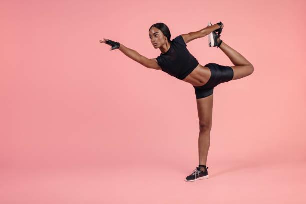 afrikanische frau üben natarajasana yoga-pose - rosa training stock-fotos und bilder