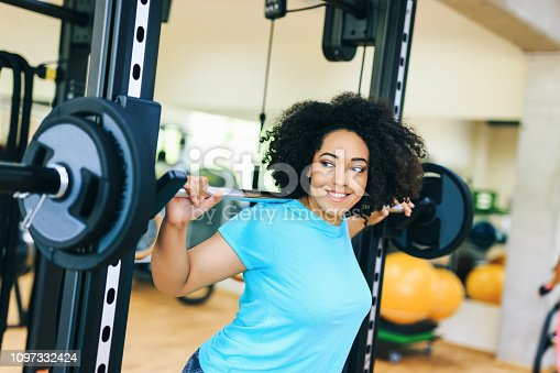 African woman practicing with barbells in fitness.