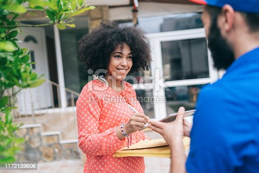 1053001624istockphoto African Woman Receiving a Delivery 1172139606