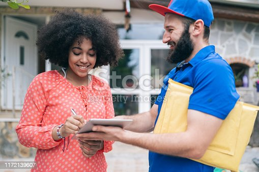 1053001624 istock photo African Woman Receiving a Delivery 1172139607
