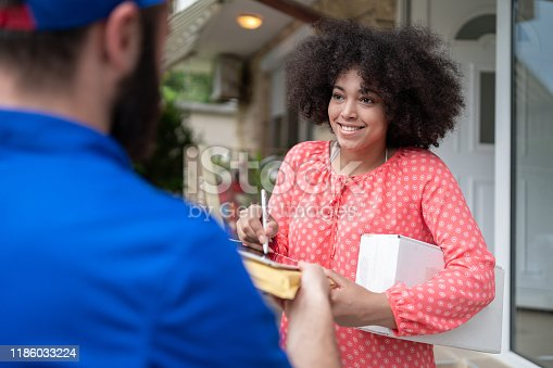 1053001624 istock photo African Woman Receiving a Delivery 1186033224