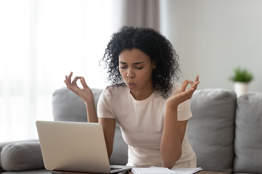 istock African woman reducing stress do yoga exercise to calm down 1186418466