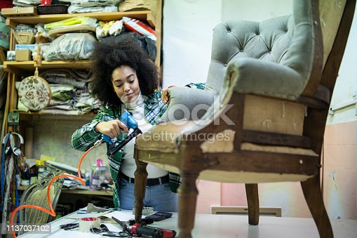 African woman renovating a chair in upholstery workshop.