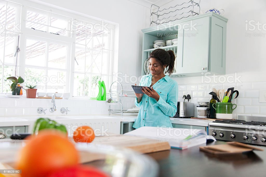 African woman searching the internet for a recipe. stock photo