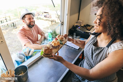 istock African woman selling burgers in food truck 1169082379