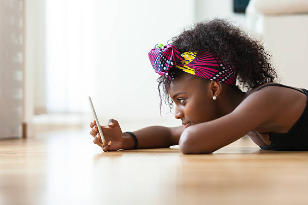 African woman sending a text message on a mobile phone stock photo