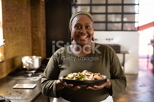 Front view of an Senior African woman at a cookery class, holding a bowl filled with vegetables. Active Seniors enjoying their retirement.