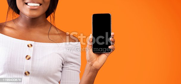 1132512759 istock photo African Woman Showing Phone Screen Over Orange Background, Cropped, Mockup 1199400876