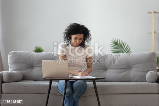 African woman sit on sofa at coffee table holding pen writing working from home, noting writing down, housewife planning week write to-do list, student learning preparing university admission concept